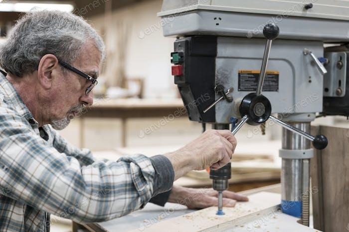 Ein älterer Mann mit Brille und Bart in einem Holzwerkergeschäft, mit einer Maschine.