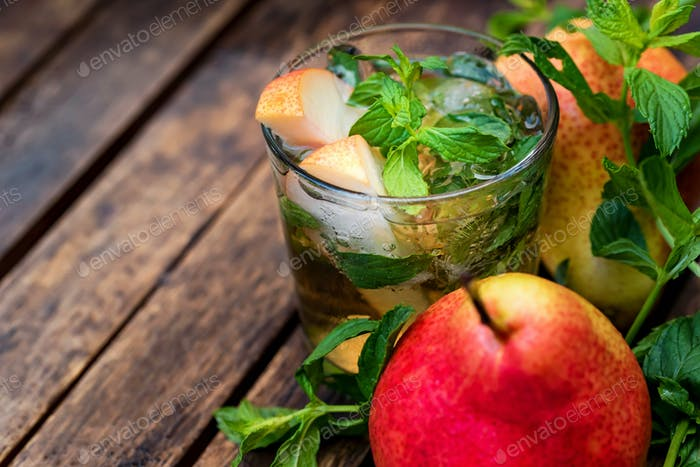 Ripe pears and pear drink on a wooden table