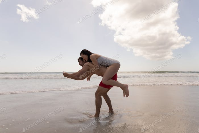 Happy young couple piggyback and  taking selfie with mobile phone at beach in the sunshine