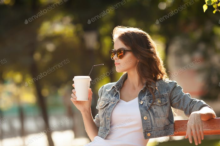Young Stylish Woman Drinking Coffee To Go In A Park
