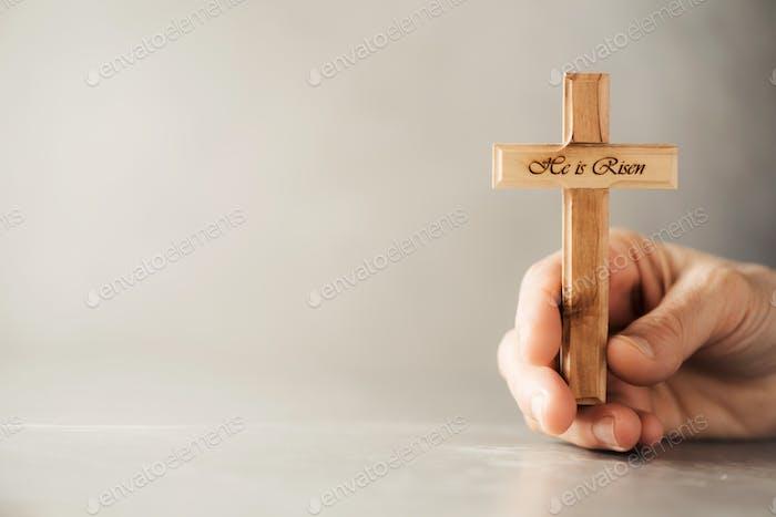 Hände halten christliches Kreuz aus Holz mit Text Er ist auf grauem Hintergrund auferstanden. Erinnerung an Jesus