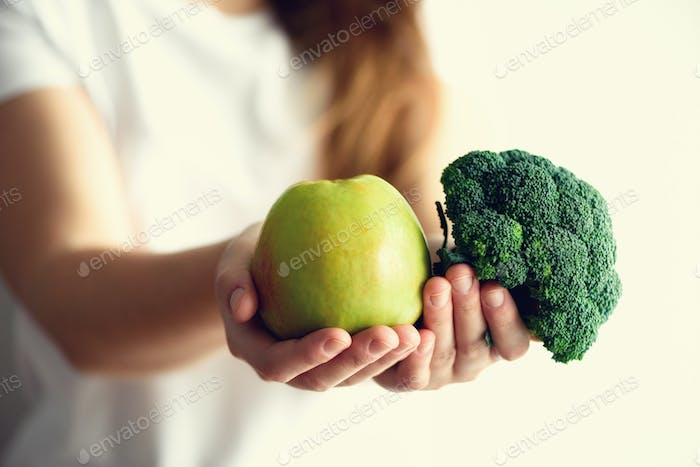 Woman in white T-shirt holding geen apple and broccoli in her hands. Copy space. Clean detox eating