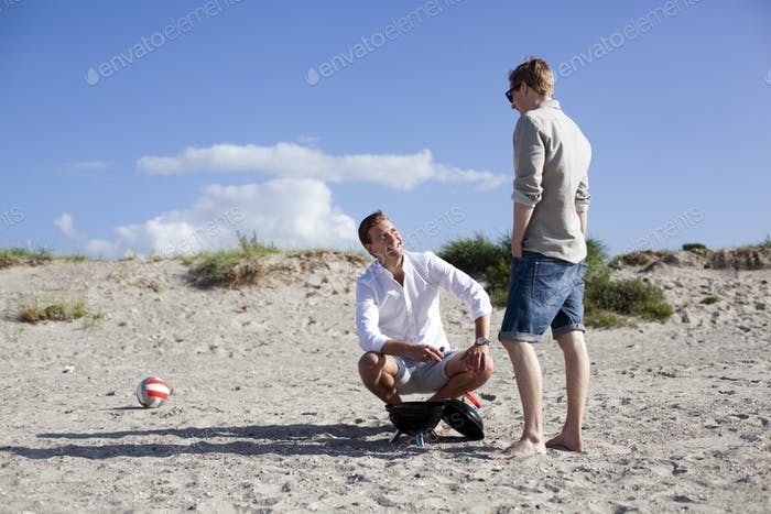 Young male friends talking while barbecuing at beach