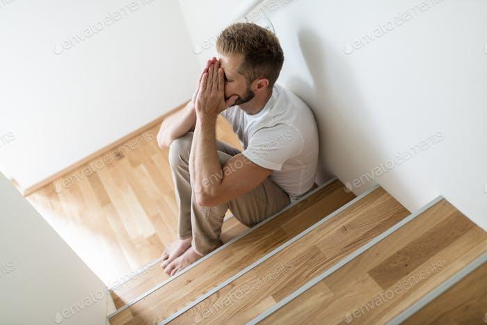 Depressive Mann zu Hause besorgt über Finanzen
