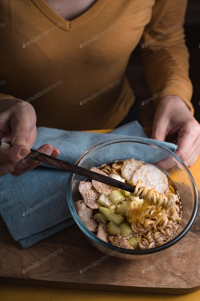 Woman eating soup with ramen noodles with chicken and celery