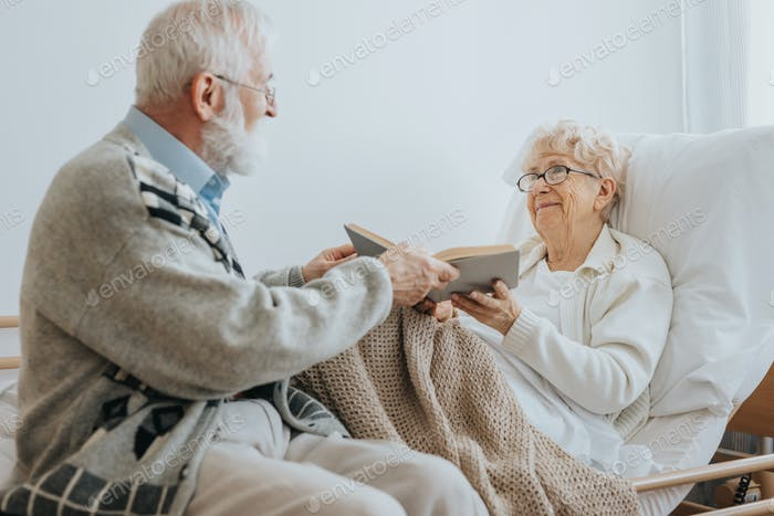 Grey elderly man hands a book to a senior friend lying on a hospital bed