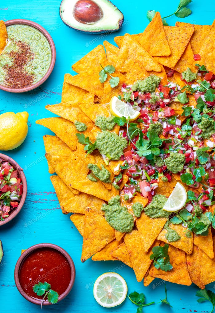 Nachos. Mexican food concept. Yellow corn totopos chips with different sauces salsas