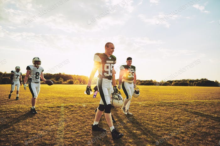 Team of American football players walking onto a field together