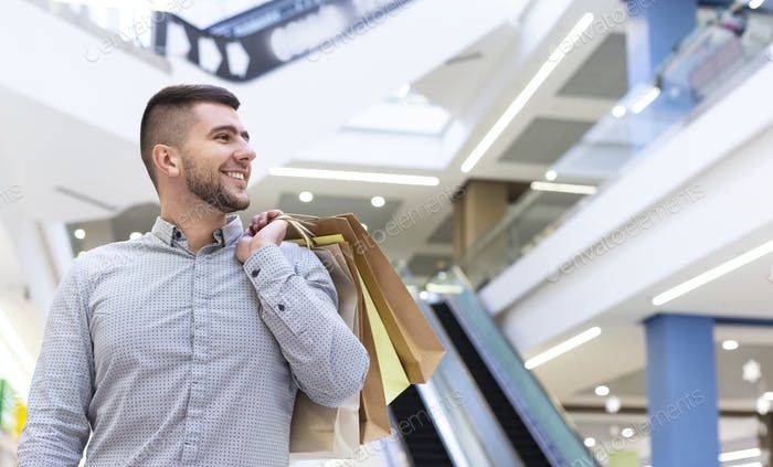 Handsome guy with purchases waiting for girlfriend