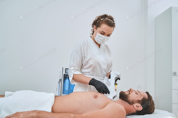 Experienced dermatologist using a mesotherapy gun during an aesthetic procedure