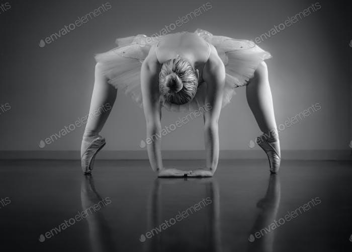 Anmutige Ballerina-Aufwärmung in Schwarz-Weiß im Ballettstudio