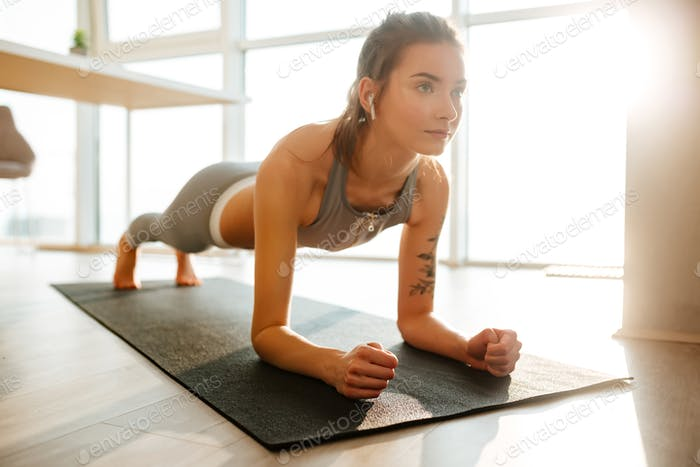Beautiful lady in sporty top and leggings practicing fitness on yoga mat listening music at home