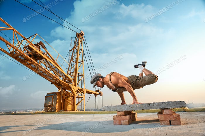 Athletic man doing exercise push ups on hands