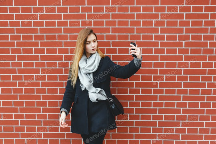 Outdoor portrait of pretty student girl taking a selfie on mobile phone