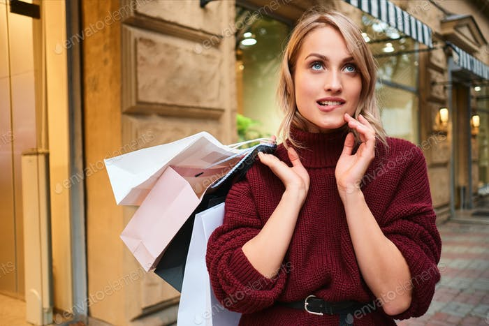 Portrait of attractive flirty blond girl with shopping bags dreaming on city street