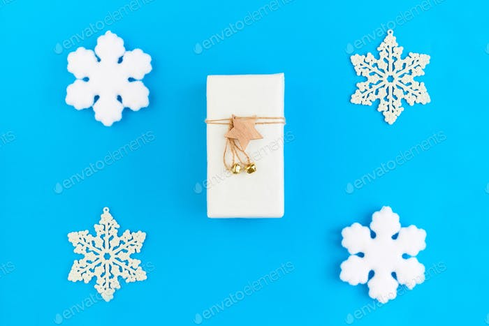 Flat layout of white package with Christmas gift with star and thread on top