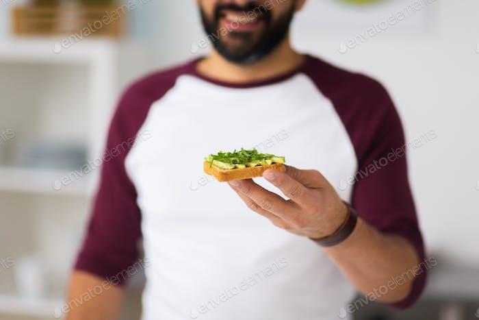 man eating avocado sandwich at home kitchen