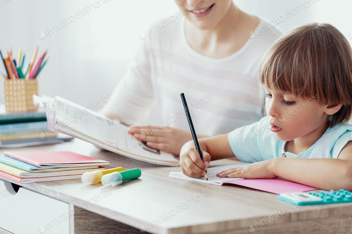 Boy doing homework and exercise during extra-curricular classes