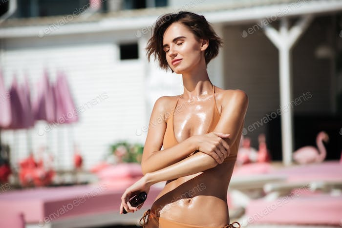 Beautiful lady in beige swimsuit using body oil for suntan