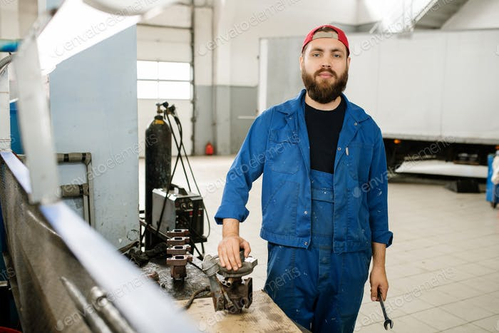 Confident young engineer of contemporary repair service standing by workplace
