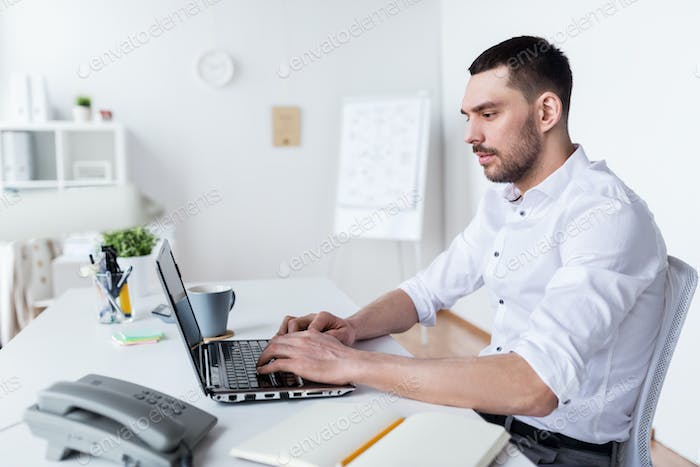 businessman typing on laptop at office