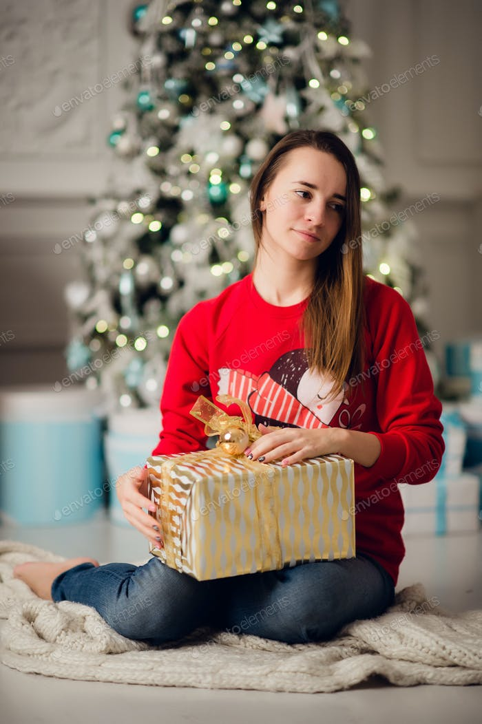 Portrait of beautiful woman with gift sitting by Christmas tree at home