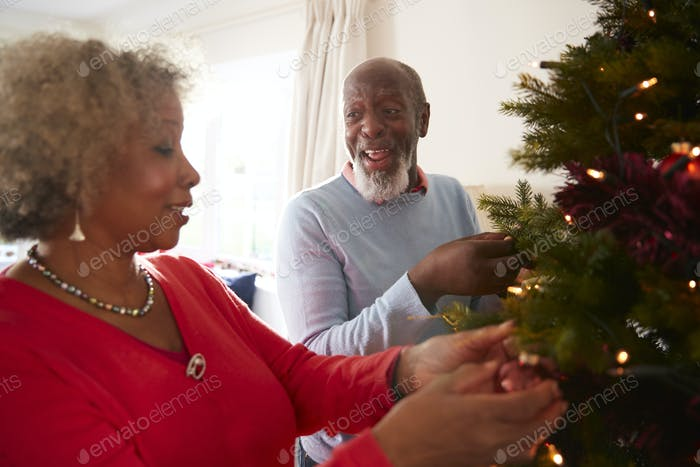 Senior Couple Hanging Decorations On Christmas Tree At Home Together