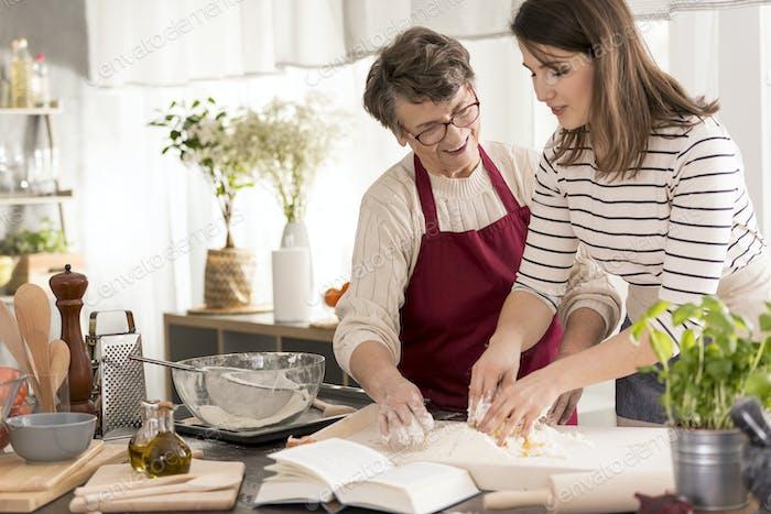 Grandmother teaching granddaughter baking cake