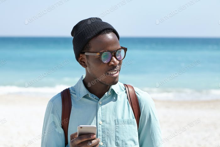 Tired Afro American backpacker in hat and eyewear using online taxi service app on mobile phone to r