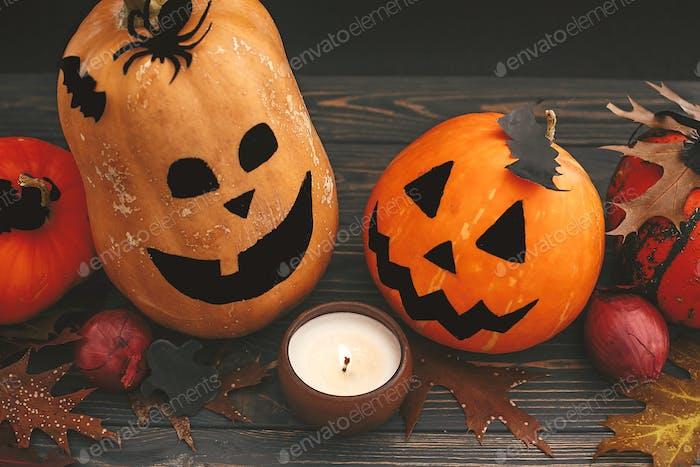Happy Halloween Konzept. Kürbisse mit gruseligen Gesichtern mit Fledermäusen, Spinne und brennender Kerze auf dunklem Holz