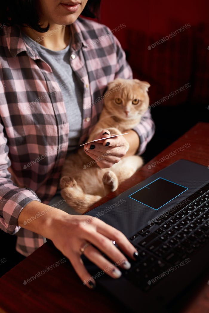 Woman wear comfy style is buying by credit card on a black notebook, laptop and cat