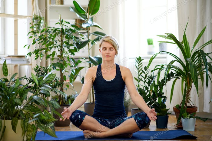 Front view of young woman indoors at home, doing yoga exercise