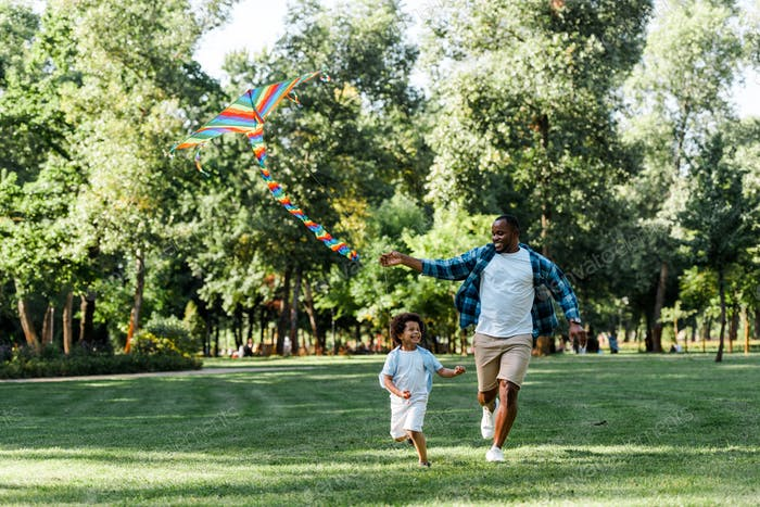 happy african american kid running with father and kite in park