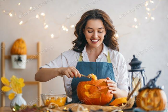 woman is carving pumpkin