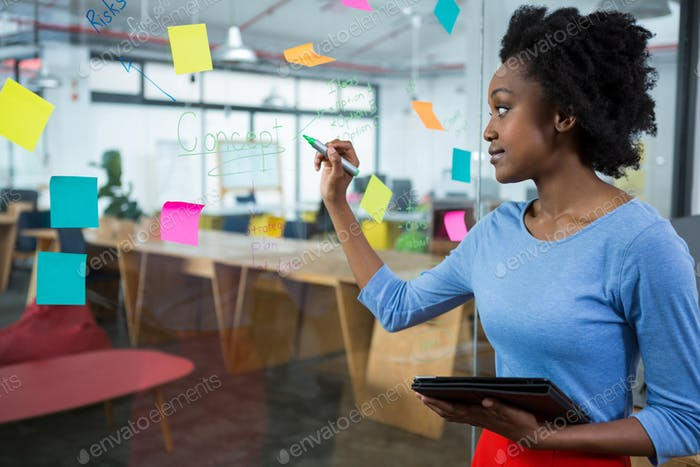 Female graphic designer writing on glass