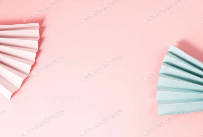 Pastel color paper fans on pink background
