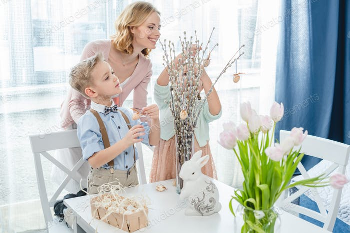 Happy mother with two children decorating willow branches with easter decorations