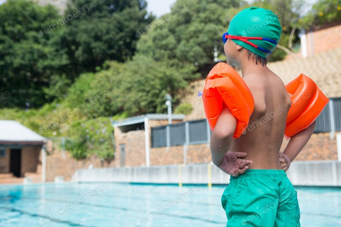 Boy wearing arm band standing at poolside