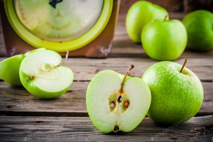 organic green apples in colander on rustic wooden background