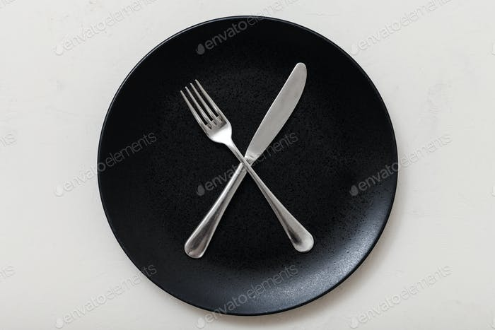 top view of black plate with cultery on white