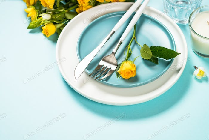 Spring table setting with flower on blue