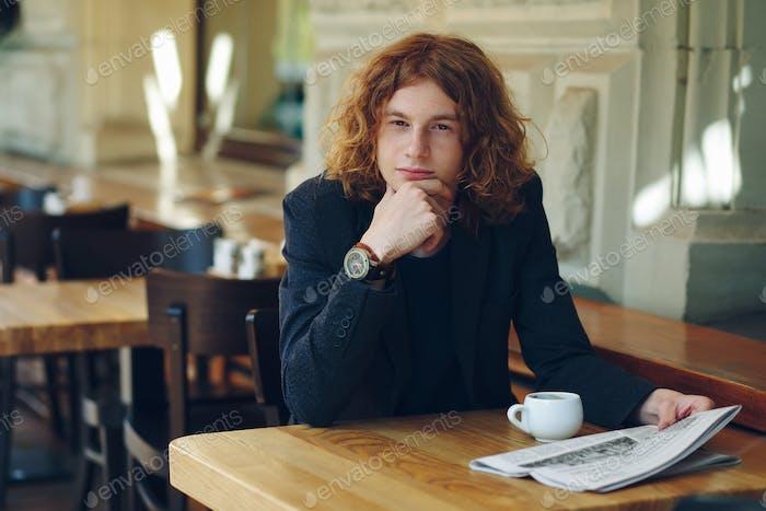 Junger Mann denken, während mit Kaffee