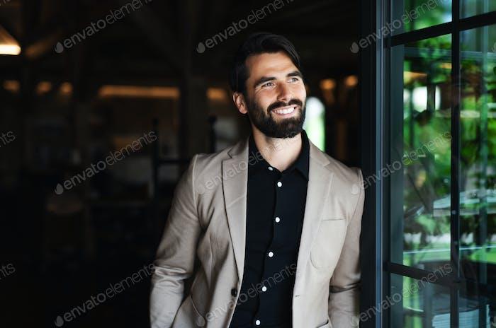 Портрет бизнесмена с курткой, стоящей в помещении ресторана