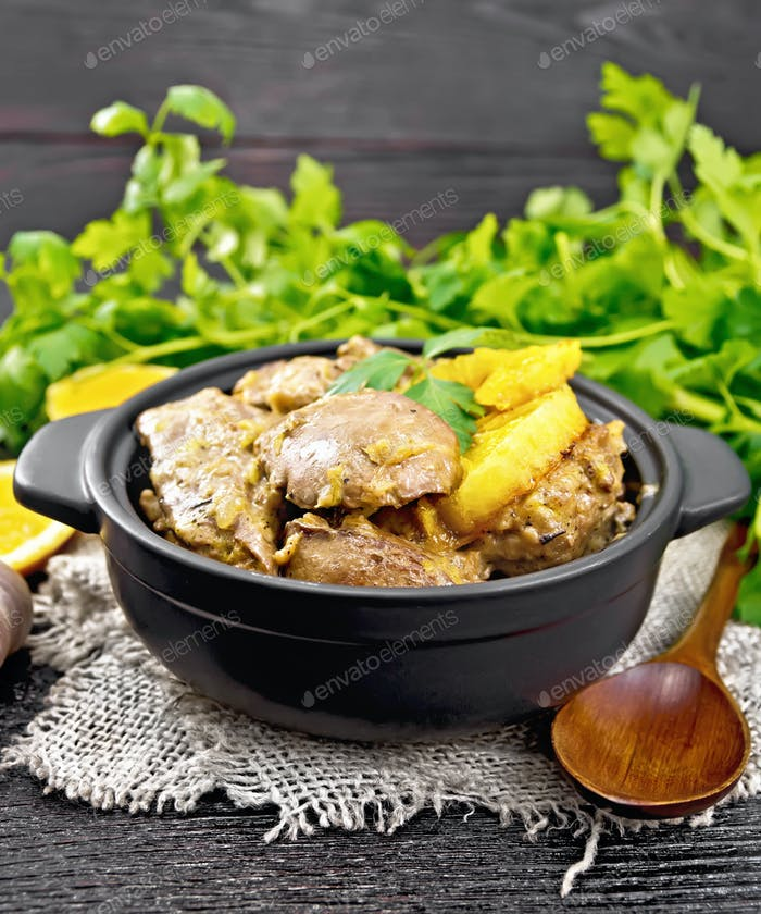 Liver with oranges in pan on burlap