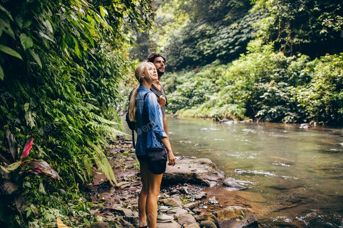 Couple standing by stream in woods