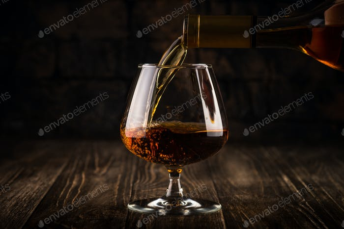 Pouring brandy or cognac in the glass