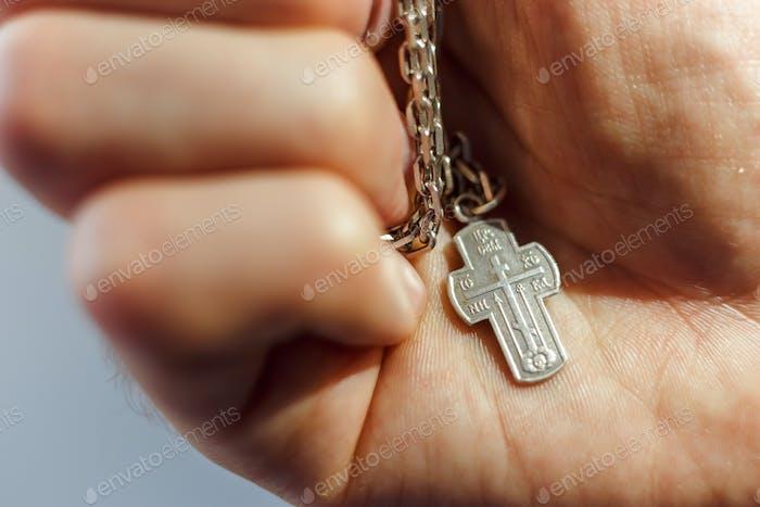 Silbernes Kreuz in der Hand mit Fokus auf das Kreuz, flache DOF
