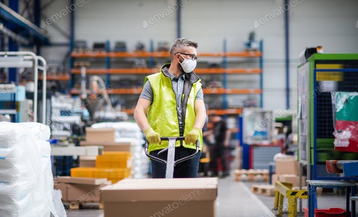 Man worker with protective mask working in industrial factory or warehouse