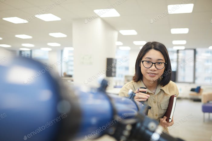 Smiling Asian Student Posing with Telescope