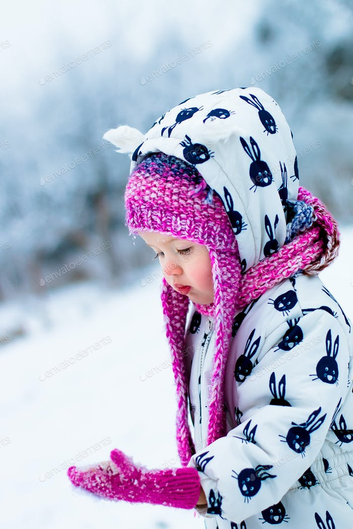 Child in snowy day. Baby girl in white snowsuit and pink hat looking on the gloves with snow.